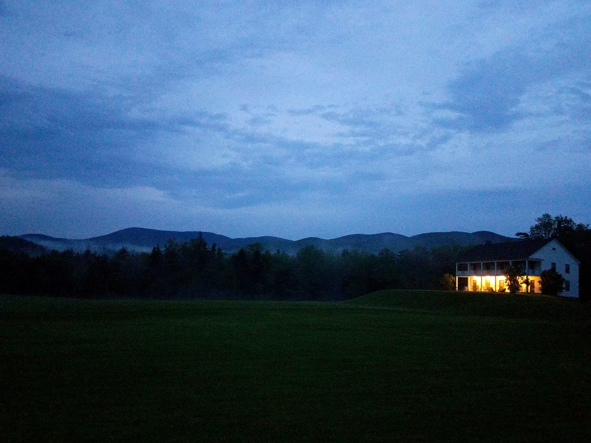 Dusk shot of a 2-story house/hotel thing situated on well-manicured greens; in the background are a line of trees and rolling mountains